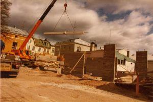En kran lyfter en balk på en byggarbetspla.