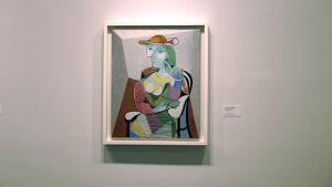 Den berömda tavlan med vit ram föreställer en dam i en tvådimensionell tappning. Damen ser till vänster med huvudet på sned. Hon har en röd smal hatt på huvudet. Hon sitter i en svart stol, iklädd en spräcklig klänning. Golvet är brunt och väggarna gråa.