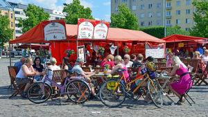 Människor sitter vid ett kafé på ett torg. Det är sommar.