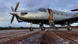 Ett silverfärgat litet passagerarflygplan står på en landningsbana av jord. Det ligger frost på marken.
