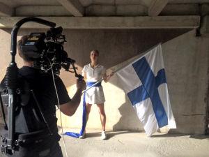 Nainen pitää suomenlippua tv-sarjan Urheilu-suomi kuvauksissa