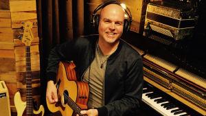 man med gitarr i musikstudio