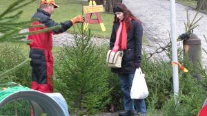 En försäljare visar en julgran åt en kvinna