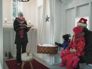 Ulkovaatteisiin pukeutunut nainen seisoo pienessä kirkossa lukemassa vanhasta raamatusta jouluevankeliumia. Viereisellä penkillä kuuntelevat nainen ja kaksi pientä lasta.