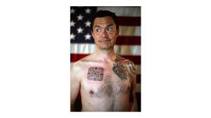 Miehen muotokuva Yhdysvaltain lippu taustalla ja Hannunvaakuna-tatuointi rinnassa.