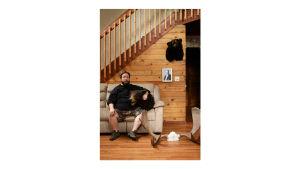 Miehen muotokuva, istuu sohvalla trofeeden ympäröimänä.