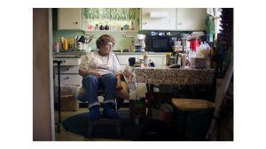 Iäkäs nainen istuu keittiössä.