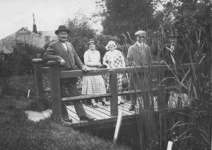Maanviljelijä Hugo Hörtsänä ja muita henkilöitä mustavalkoisessa valokuvassa puutarhassa, otettu 30-luvulla Hörtsänän arboretumissa Orivedellä.