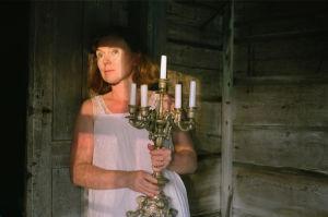 Nainen pitelee  kynttelikköä kädessä.