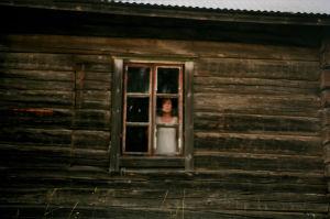 Nainen katsoo ulos mökin ikkunasta.