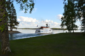 Valkoinen, pieni matkustajalaiva suuntaa kanavasta kohti järvenselkää.