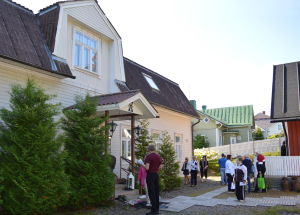 Puutaloalueella usea mansardikattoinen talo, erään talon pihamaalla ihmisiä seisoskelemassa.