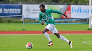 EIF:s Paul Akouokou löper med bollen på fotbollsplanen.