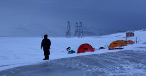 En person står bredvid några tält. Det ser ut som om hen håller vakt. Runt omkring syns snö och berg.