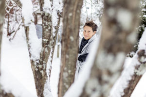 Heini Hirvonen ulkona, katsoo kameraan puitten runkojen välistä.