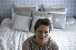 Heini Hirvonen istuu sängyn päädyssä ja katsoo kameraan.
