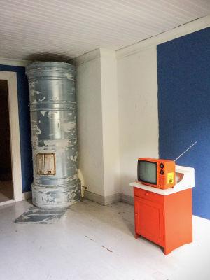 Valkoisessa huoneessa vanha pönttöuuni ja oranssi matkatelevisio.