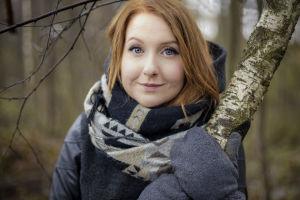 Tiia Ung metsässä, pitää kiinni koivun rungosta.
