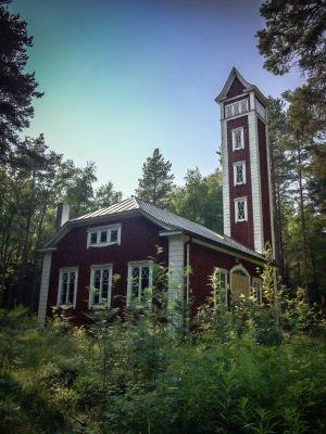 Ulkokuva paloasemasta, vanha punamullalla maalattu rakennus, valkoiset nurkkalaudat ja ikkunanpielet, ympärillä kesäistä metsää, kuvattu Varjakansaaren vanhassa sahakylässä.