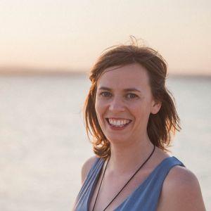 En kvinna med axellångt hår och en grön ärmlös blus. Hon står på en strand och i bakgrunden syns horisonten.