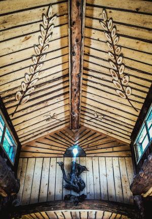 Sisällä Julumetun salissa Kammi-kylässä, päätyseinässä puusta tehty lintumainen koriste, lasinen ikkuna josta loistaa valoa, katossa puusta leikattuja oksamaisia koristeita.