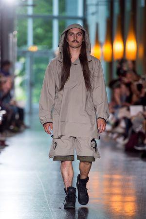 En manlig modell som går på catwalken. Han är iklädd beige shorts och en beige parkas.