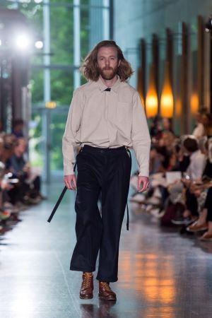 En man som går på en catwalk. Han är iklädd svarta byxor och en beige skjorta.