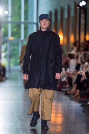 En manlig modell som går på en catwalk. Han är klädd i beige byxor, en mörkblå jacka och en mörkblå keps.