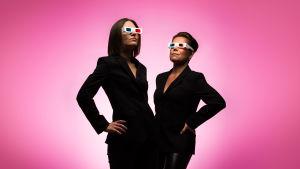 Kaksi mustiin jakkuihin pukeutunutta naista 3D-lasit päässä pinkin värisessä tilassa