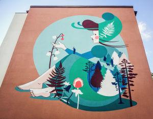 Kerrostalon päätyyn maalattu suurikokoinen maalaus, jossa tyttöhahmo, metsää, tytön polvella mies.