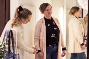 Två kvinnor i ett provrum. Den ena tittar sig i spegeln eftersom hon provar en kofta, och den andra viker upp hennes ena koftärm.