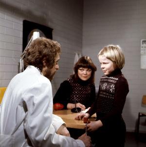 Villahousupakko-elokuvassa 1977 Timo (Kyösti Väntänen) lääkärin (Esa Pakarinen junior) vastaanotolla, taustalla opettaja (Pirkkoliisa Tikka)