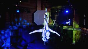Kaksi sirkustaiteilijaa pää alaspäin tekemässä temppua, ojentavat jalkoja vastakkaisiin suuntiin.