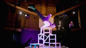 sirkustaiteilija seisoo käsillään tuolien päällä