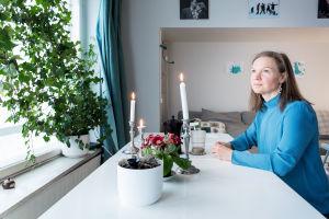 Petriikka Pohjanheimo istuu kahvikupin kanssa pöydän ääressä ja katselee ulos.