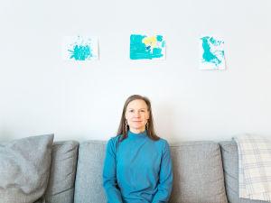 Petriikka Pohjanheimo istuu sohvalla ja katsoo kohti kameraa.