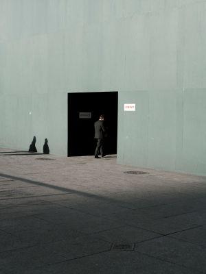 Mies astuu sisään oviaukosta harmaassa ympäristössä.