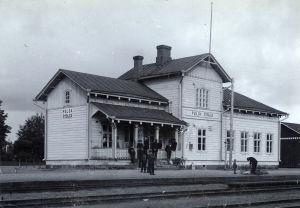 Mustavalkoinen arkistokuva vanhasta puisesta rautatieasemasta, edessä henkilöitä odottamassa, 1900-luvun alkua.