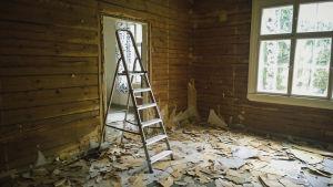 Remontin keskellä oleva hirsitalo, lattialla remonttiroskia, tikkaat.