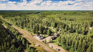 Ilmakuva vanhasta rautatieasemasta, ympärillä metsää, taustalla taivas.