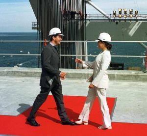Man och kvinna iförda kostym och skyddshjälm går mot varandra på röd matta