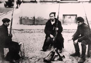 Kolme punakaartin partioon kuuluvaa miestä nuotion ääressä kadulla Pietarissa 1917.