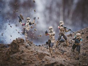 Fyra leksaksfigurer föreställande soldater från Star wars. De står på sand om en av dem verkar ha stigit på en mina. Det sprättar upp sand framför honom.