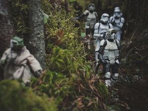 Leksaksfigurer föreställande soldater från Star wars. De går i en skog och i förgrunden syns en annan figut som gömmer sig.