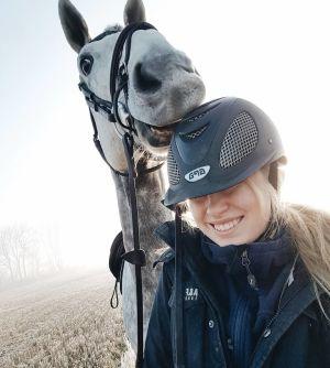 En ung kvinna med en ridhjälp på huvudet. En silvergrå häst har sin mule mot ridhjälmen. Både hästen och kvinnan ser glada ut.