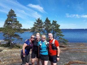 Kolme naista ja mies poseeraavat kameralle kauniin järvimaiseman edessä