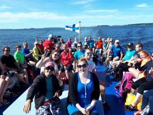 Iso ryhmä ihmisiä istuu iloisena veneessä. Suomen lippu heiluu tuulessa