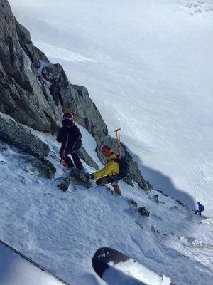 Tre personer klättrar upp för en snöig bergsvägg. De har på sig skidor. Stavarna har de i sina ryggsäckar. Det är en brant bergsvägg.