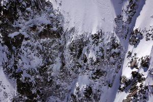 En bergsvägg. Tittar man nog ser man en person som håller på att åka ner för berget med slalomskidor. Personen ser pytteliten ut, och skidorna lämnar spår i snön.