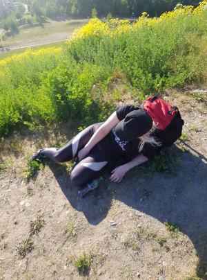 En kvinna iklädd vandringskläder halvligger i en backe. Det ser ut som att hon tycker det är mycket tungt.